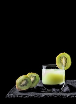 Kiwi juice with ice on black background and two pieces of kiwi