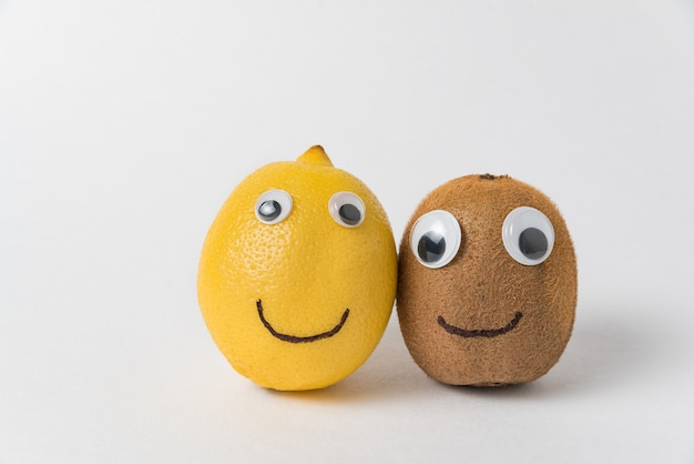 Kiwi and lemon with googly eyes and smiles on white background. friendship concept