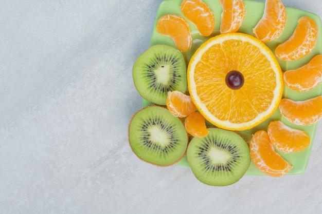 녹색 접시에 키위, 오렌지, 귤 조각. 고품질 사진