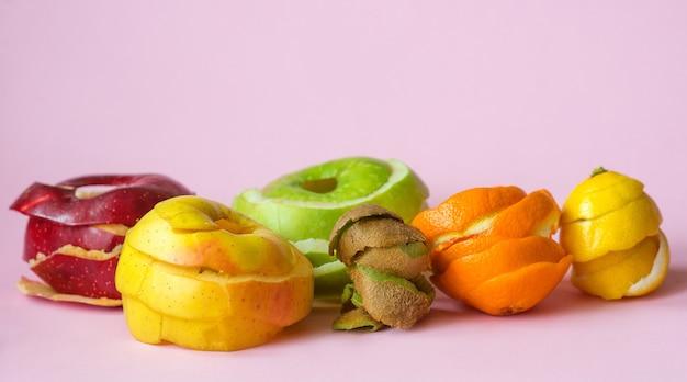 キウイオレンジレモンと赤、緑、黄色のリンゴは、リサイクルのシンボルとしてピンクの背景に皮をむく