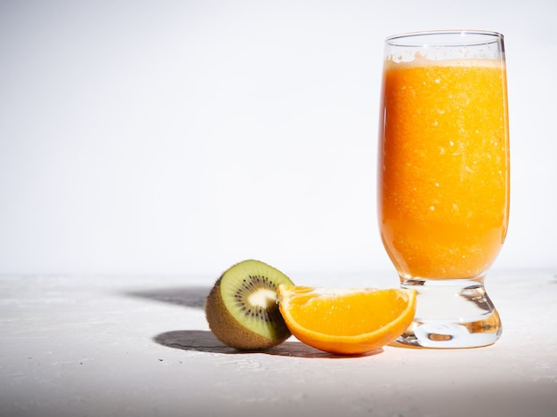 Kiwi and orange smoothies in a glass cup on a white background with shadows. copyspace.