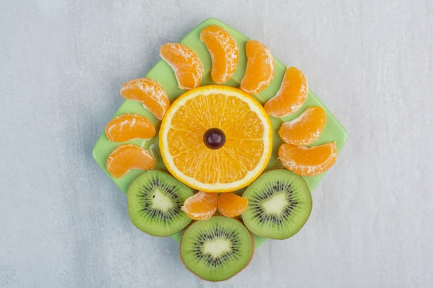 Kiwi, orange and tangerine slices on green plate. high quality photo