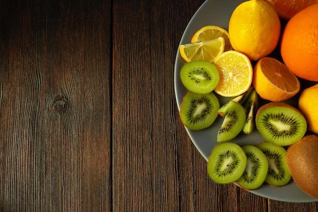 Киви, апельсины и лимоны на тарелке на темном деревянном столе