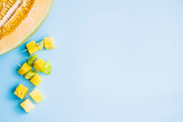 Kiwi and pineapple canape near halved melon on blue backdrop