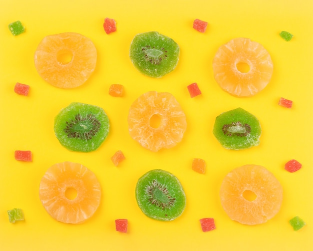 Kiwi and pineapple dried fruits near to candied fruits, sweet colorful background