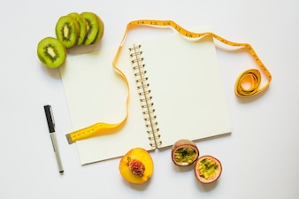 Kiwi slices; peach and passion fruits with measuring tape; pen and spiral notebook