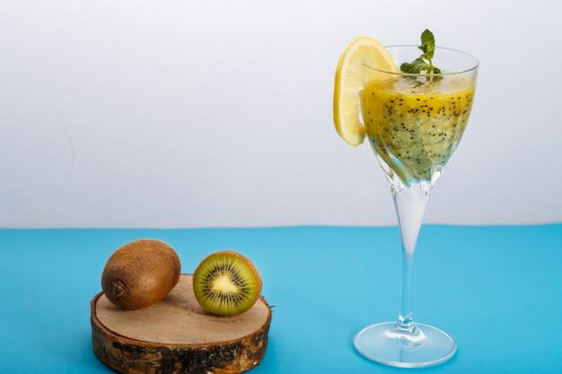 Смузи из киви, украшенный мятой и лимоном в стакане на синей поверхности рядом с киви