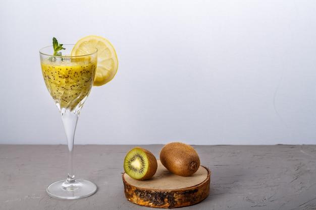 Смузи из киви, украшенный мятой и лимоном в стакане на серой поверхности рядом с киви