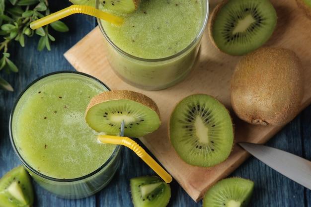 푸른 나무 테이블에 신선한 키 위 슬라이스 옆 유리에 키 위 스무디. 과일 음료. 평면도