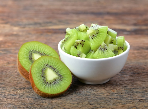 Kiwi in a white bowl on wooden table