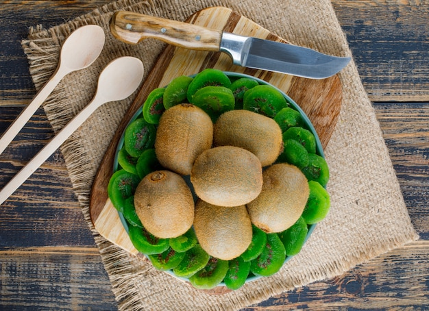 Kiwi with dried slices, cutting board, knife, spoons in a plate on wooden and piece of sack background, flat lay.