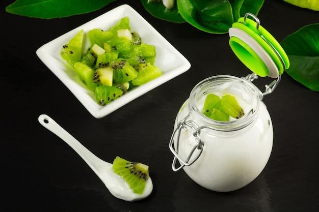 Kiwi yogurt with fruit over ardesia