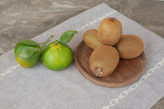 Киви и свежие мандарины на серой скатерти.