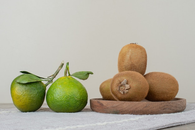 Kiwis and fresh tangerines on gray tablecloth.