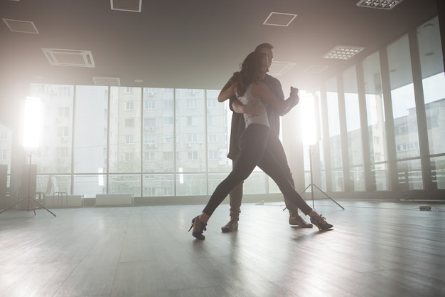 大きな窓を背景にしたダンスルームの前でキゾンバを踊る情熱を示すキゾンバダンサー。情熱的なダンサー。