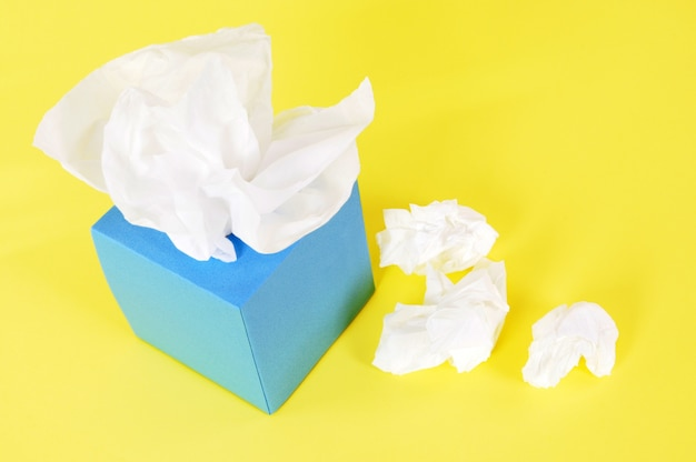 Kleenex style tissues on yellow background