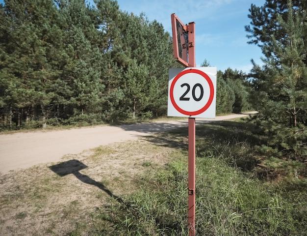 Км в час знак ограничения скорости возле грунтовой дороги на природе