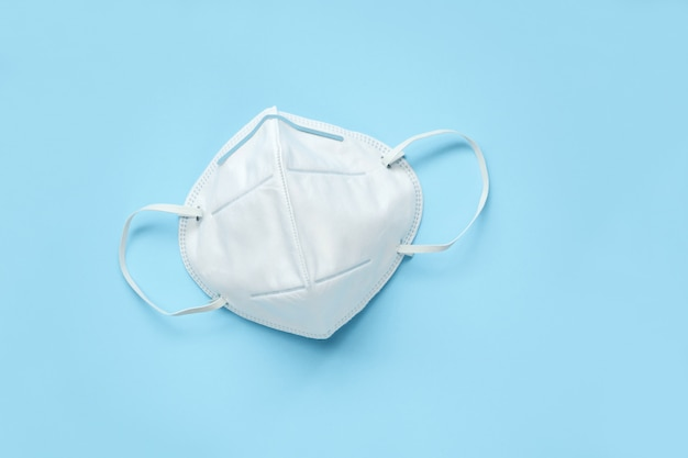 Kn95 face mask on blue background protection against pm 2.5 polution and covid-19 coronavirus. healthcare and medical concept