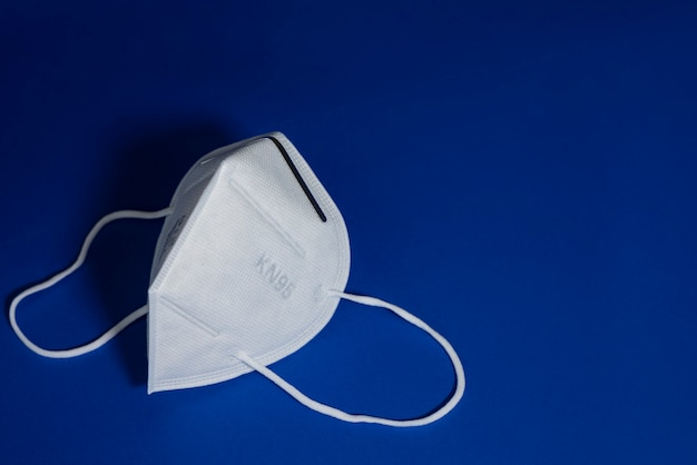 Kn95 or n95 white mask with antiviral medical mask for protection against coronavirus on blue