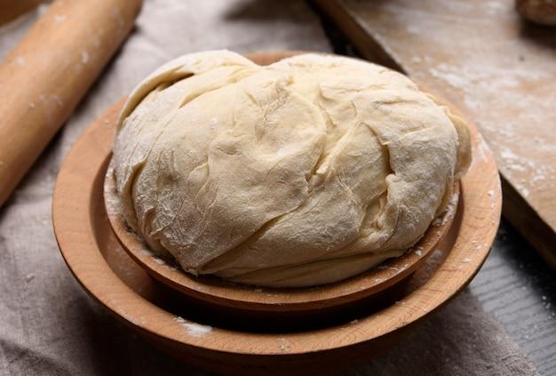 Замесить тесто из белой пшеничной муки в деревянной тарелке, крупным планом