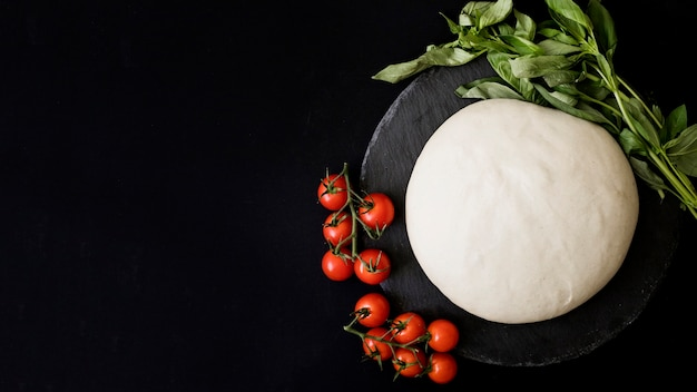 Kneaded uncooked dough; red cherry tomatoes and basil on slate against black background