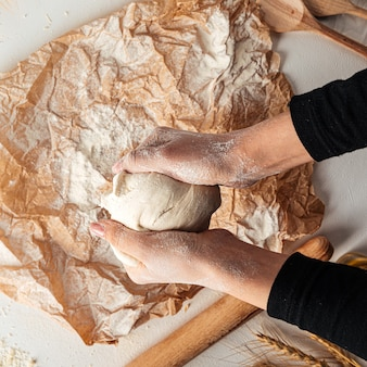 Kneading dough for pizza cooking on the paper