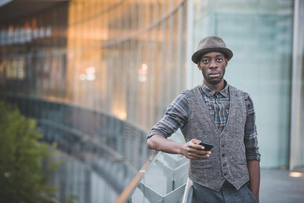 Колено фигура молодой красивый человек афро, проведение смартфон, опираясь на поручень