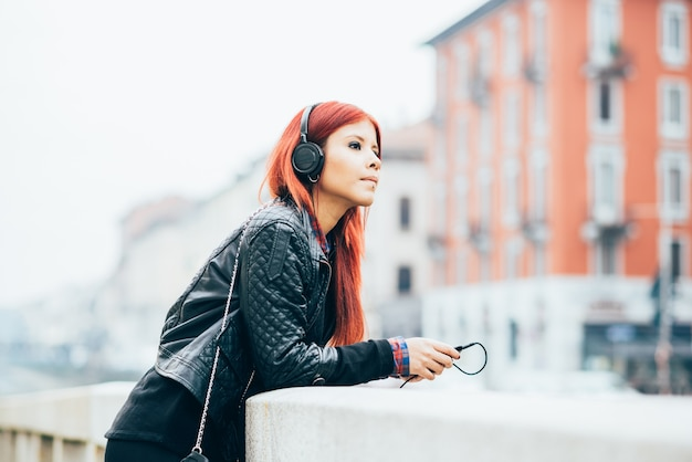 Knee figure of young beautiful hispanic redhead woman listening music with headphones