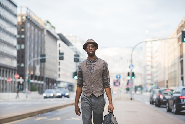 Knee figure of young handsome afro black man walking in the street of the city