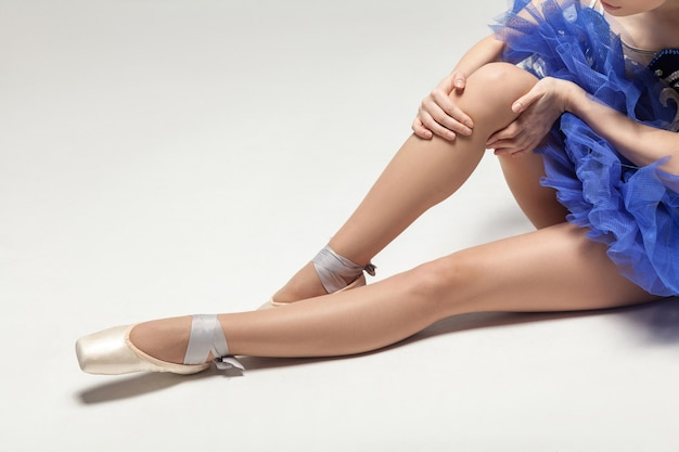 Knee pain ballerina blue dress and in pointe shoes sitting on white floor closeup