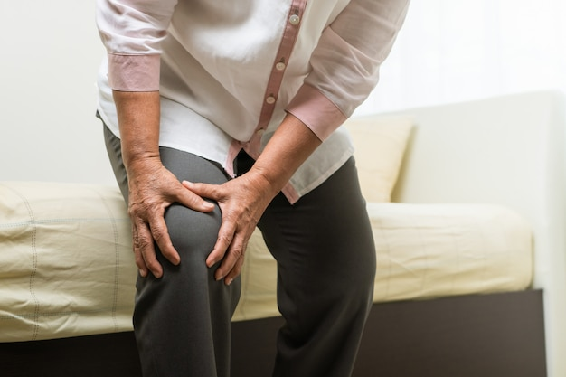Knee pain of old woman at home