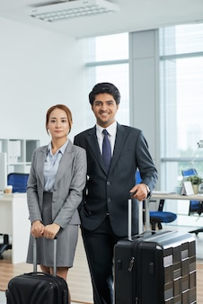 Knee-up shot of man and woman in suits posing in office with suitcases before business trip
