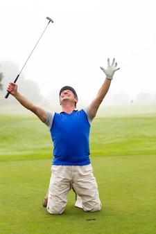 Kneeling golfer cheering on putting green