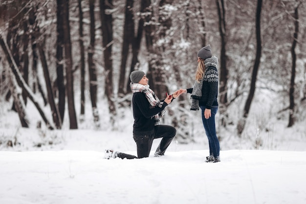 Kneeling guy puts an engagement ring on a girl's hand, making a proposal to get married in winter in a snowy forest