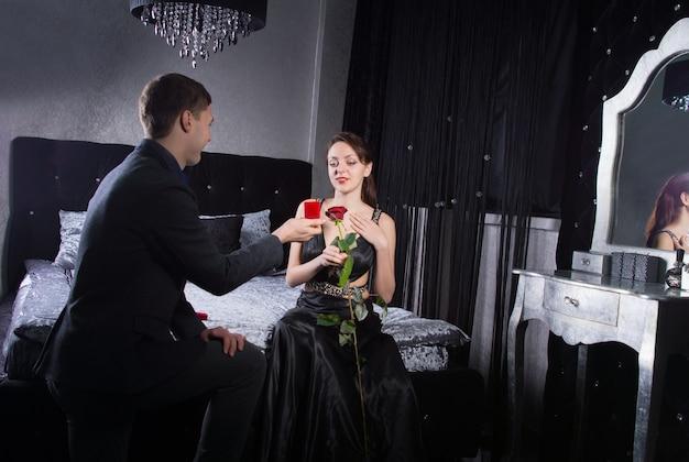 寝室にいる間、彼の幸せなかわいいガールフレンドに宝石の贈り物を提供するひざまずく若い男。