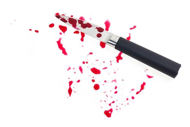Нож и капля крови на белом фоне.
