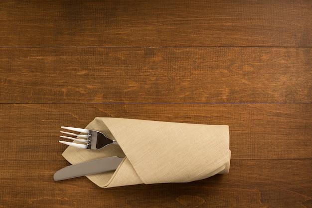 木製の背景にナプキンでナイフとフォーク