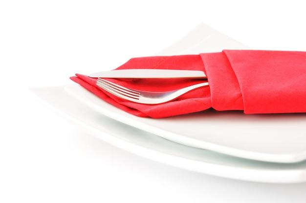 Нож и вилка в красной салфетке на белой двойной квадратной тарелке на белом фоне