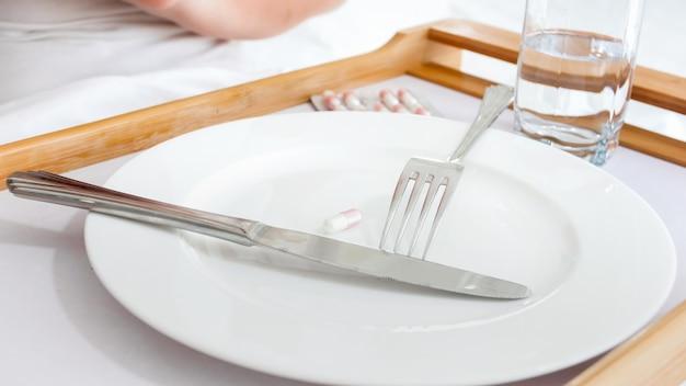 丸薬や錠剤の横にある空の皿の上に横たわっているナイフとフォーク。ダイエット、減量、薬の概念。