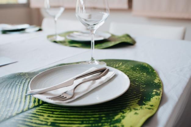 白い皿の上のナプキンに置かれたナイフとフォーク。結婚式のシートに配置