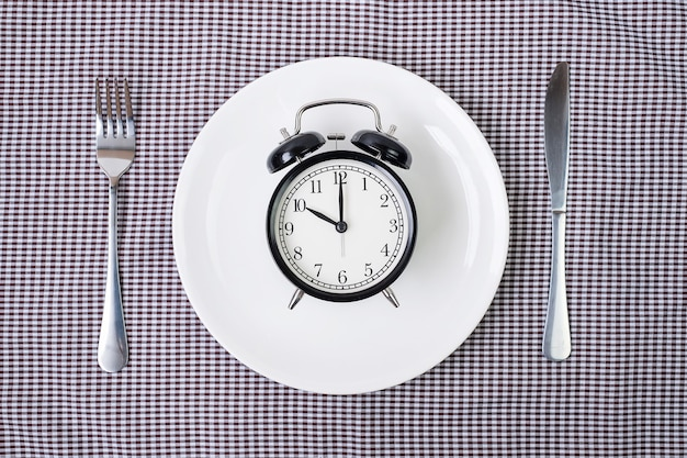 Нож и вилка с будильником на белой тарелке на фоне скатерти.
