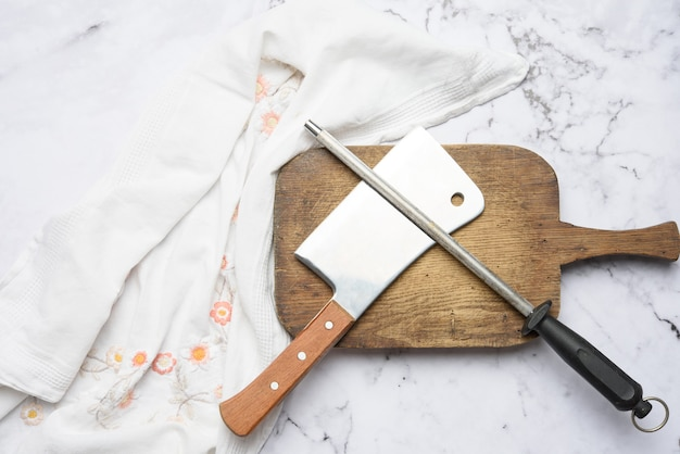 Нож и старая железная точилка с ручкой для кухонных ножей на белом фоне, вид сверху