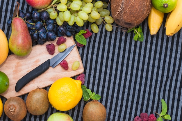 Knife on chopping board with various type of fresh fruits on striped pattern tablecloth