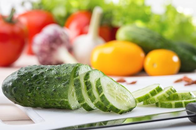 Нож, кружочки свежих огурцов, чеснок и другие ранние овощи.