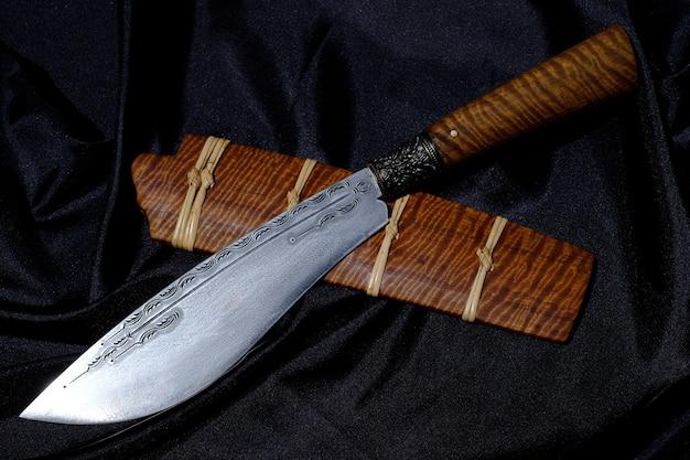 Нож нестандартный или enep в ножнах из натурального дерева на фоне старого стола ручной работы из таиланда
