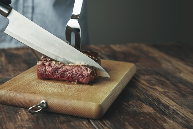 Knife cut slice of grilled meat on wooden board in front of big steel fork in steak.