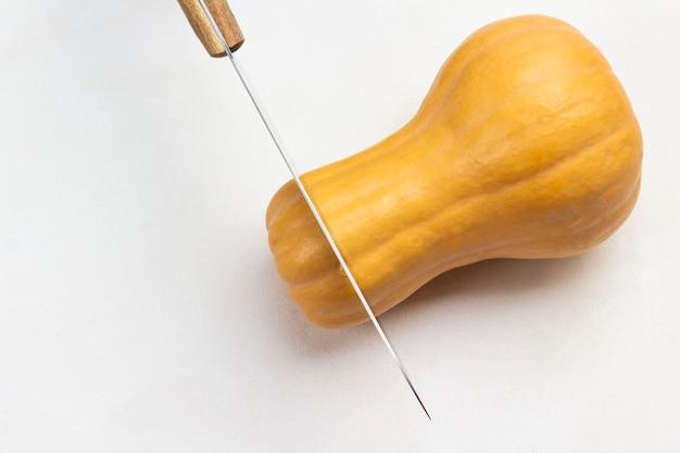 ナイフはカボチャ全体を切ります。 spaseをコピーします。白色の背景。上面図。