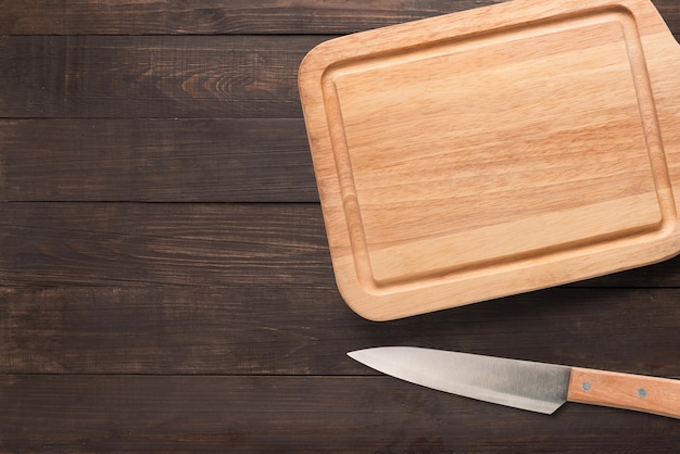 Knife and cutting board on the wooden background. copy space for your text