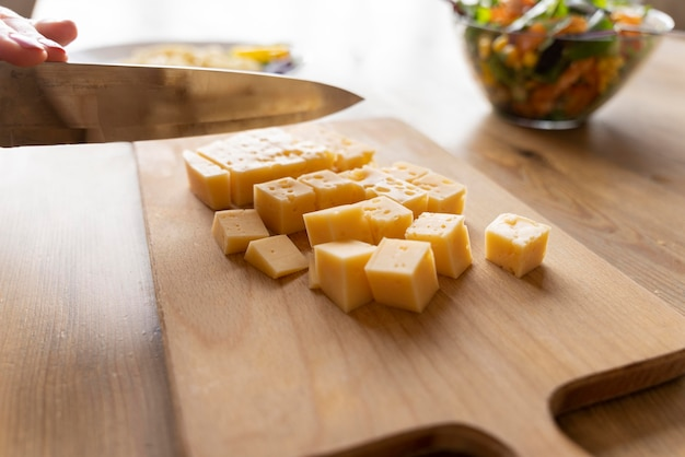 Knife cutting cheese on wooden board