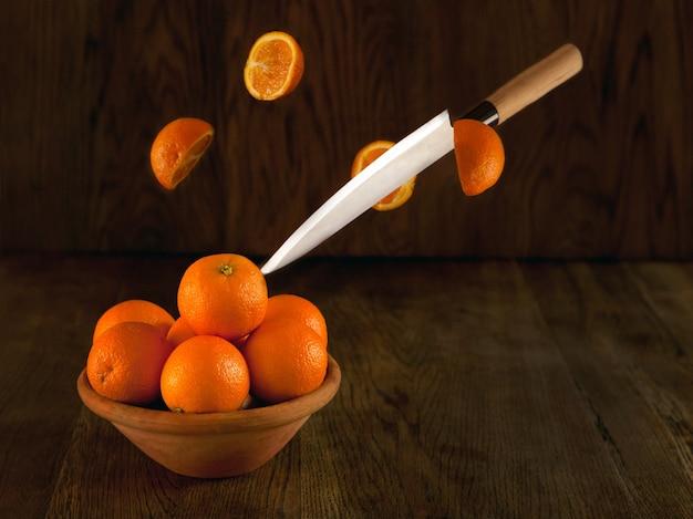 칼로 오렌지를 자르는 오렌지 많은 그릇 그릇에서 오렌지를 날리거나 사진으로 이동